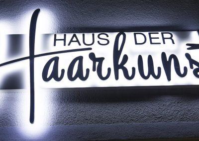 Salon Außenansicht leuchtendes Logo Haus der Haarkunst Haag